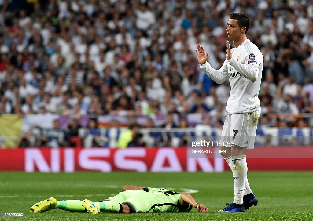 Real Madrid's Portuguese forward Cristiano Ronaldo (R) gesture as he Manchester palyer is lying on the ground during the UEFA Champions League semi-final second leg football match Real Madrid CF vs Manchester City FC at the Santiago Bernabeu stadium in Madrid, on May 4, 2016. / AFP / GERARD