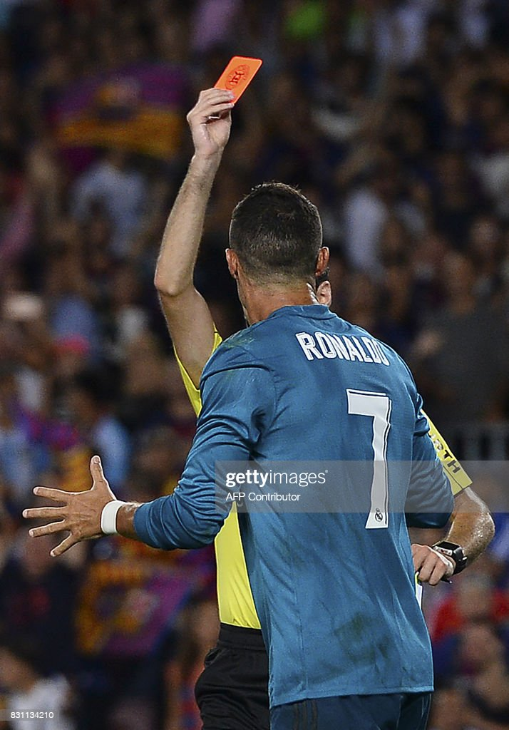 Real Madrid's Portuguese forward Cristiano Ronaldo (front) gestures after receiving a red card by the referee during the first leg of the Spanish Supercup football match between FC Barcelona and Real Madrid CF at the Camp Nou stadium in Barcelona on August 13, 2017. / AFP PHOTO / Josep LAGO