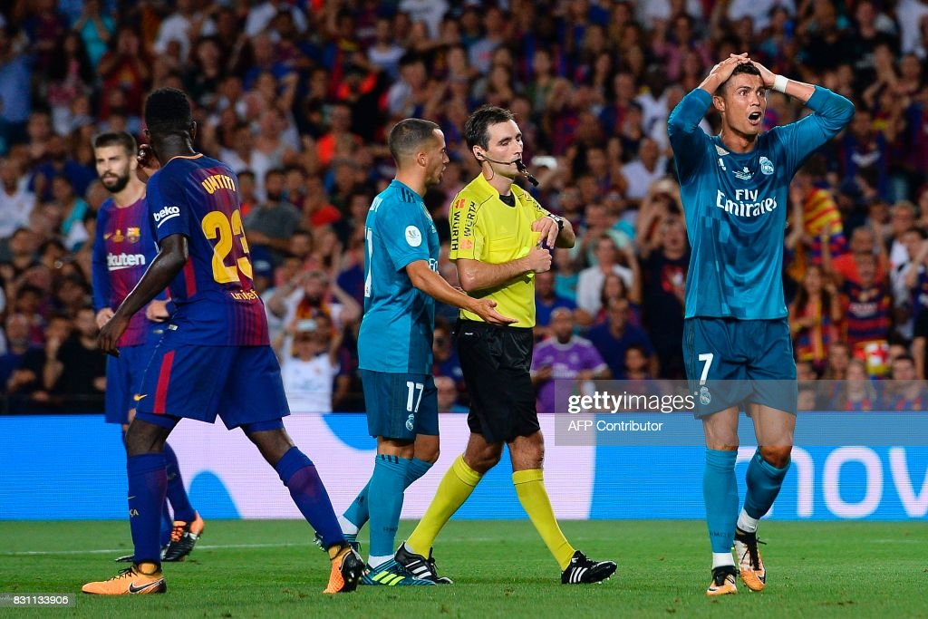 Real Madrid's Portuguese forward Cristiano Ronaldo (R) gestures after receiving his second yellow card by referee Ricardo de Burgos Bengoetxea (2R) during the first leg of the Spanish Supercup football match between FC Barcelona and Real Madrid CF at the Camp Nou stadium in Barcelona on August 13, 2017. / AFP PHOTO / Josep LAGO