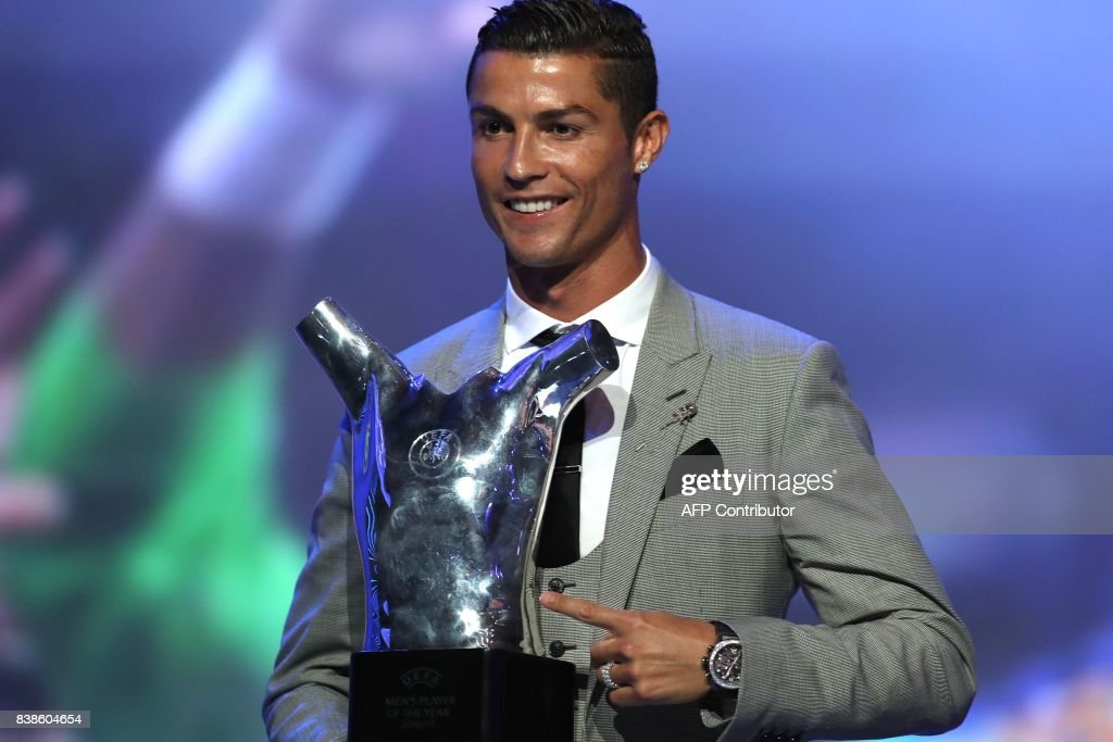 TOPSHOT - Real Madrid's Portuguese forward Cristiano Ronaldo gestures as he poses with the trophy after he was awarded the title of 'Best Men's Player in Europe' at the conclusion of the UEFA Champions League group stage draw ceremony in Monaco on August 24, 2017. /