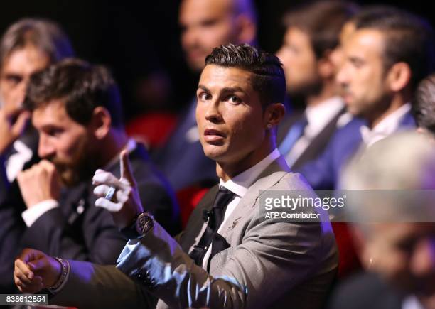 Real Madrid's Portuguese forward Cristiano Ronaldo gestures as he sits alongaide Barcelona's Argentinian forward Lionel Messi as they wait ahead of...