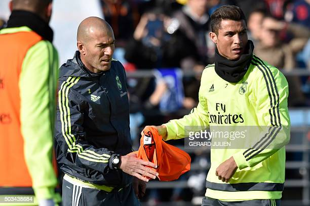 Real Madrid's Portuguese forward Cristiano Ronaldo gives a bib to Real Madrid's new French coach Zinedine Zidane during his first training session as...