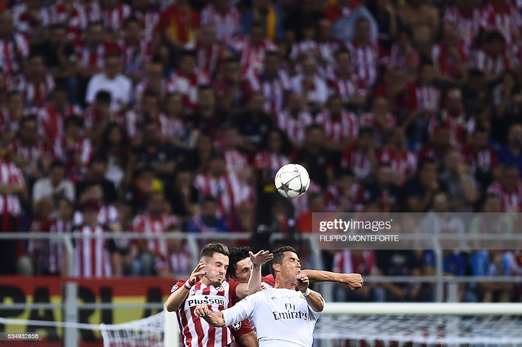 Real Madrid's Portuguese forward Cristiano Ronaldo (R) heads the ball next to Atletico Madrid's Spanish midfielder Saul Niguez (L) during the UEFA Champions League final football match between Real Madrid and Atletico Madrid at San Siro Stadium in Milan, on May 28, 2016. / AFP / FILIPPO