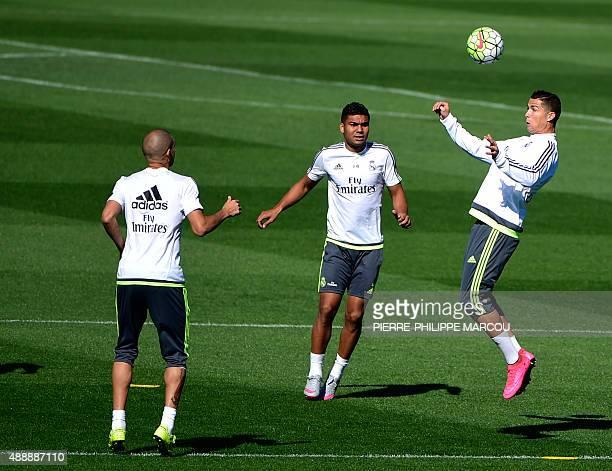 Real Madrid's Portuguese forward Cristiano Ronaldo heads the ball past Real Madrid's Portuguese defender Pepe and Real Madrid's Brazilian midfielder...