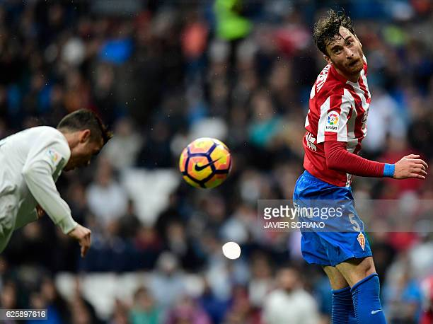 Real Madrid's Portuguese forward Cristiano Ronaldo heads the ball to score his second goal beside Sporting Gijon's Venezuelan defender Fernando...
