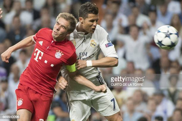 Real Madrid's Portuguese forward Cristiano Ronaldo heads the ball to score beside Bayern Munich's defender Philipp Lahm during the UEFA Champions...