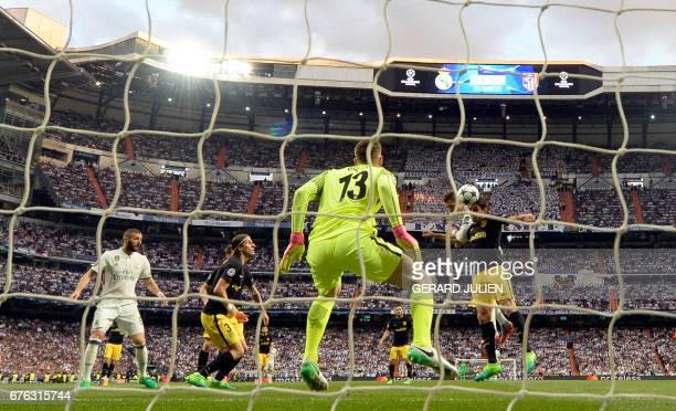 Real Madrid's Portuguese forward Cristiano Ronaldo heads to score past Atletico Madrid's Slovenian goalkeeper Jan Oblak during the UEFA Champions...