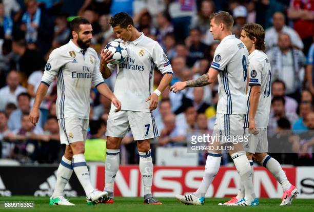 Real Madrid's Portuguese forward Cristiano Ronaldo holds the ball beside Real Madrid's defender Dani Carvajal Real Madrid's German midfielder Toni...