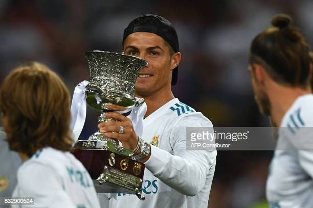 Real Madrid's Portuguese forward Cristiano Ronaldo holds up the trophy as he celebrates their Supercup after winning the second leg of the Spanish...