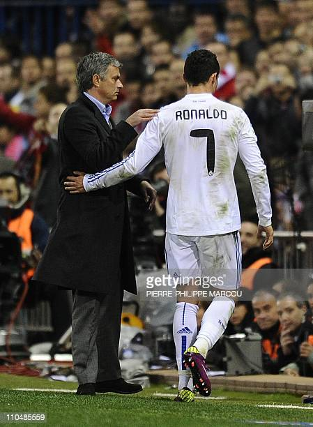 Real Madrid's Portuguese forward Cristiano Ronaldo is greeted by Real Madrid's Portuguese coach Jose Mourinho as he leaves the field during their...
