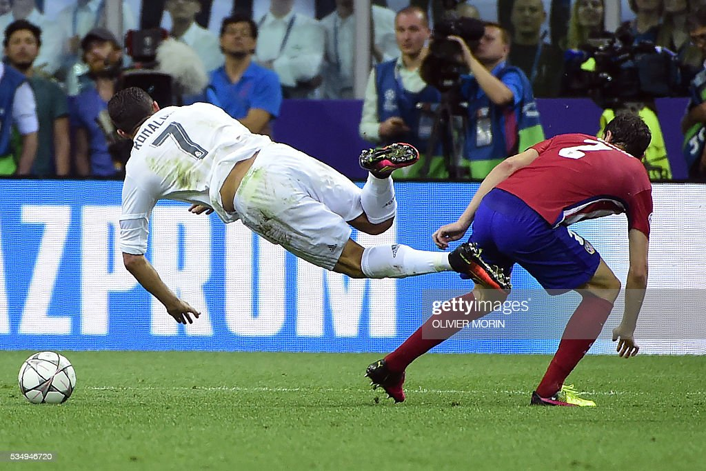 Real Madrid's Portuguese forward Cristiano Ronaldo (L) is tackled by Atletico Madrid's Uruguayan defender Diego Godin during the UEFA Champions League final football match between Real Madrid and Atletico Madrid at San Siro Stadium in Milan, on May 28, 2016. / AFP / OLIVIER