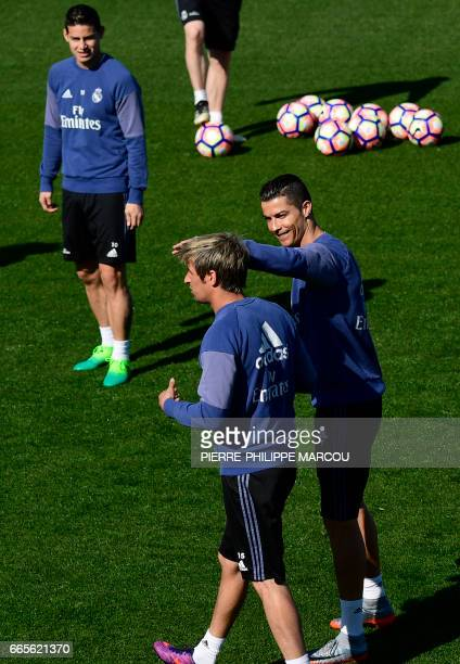 Real Madrid's Portuguese forward Cristiano Ronaldo jokes with Real Madrid's Portuguese defender Fabio Coentrao during a training session at...