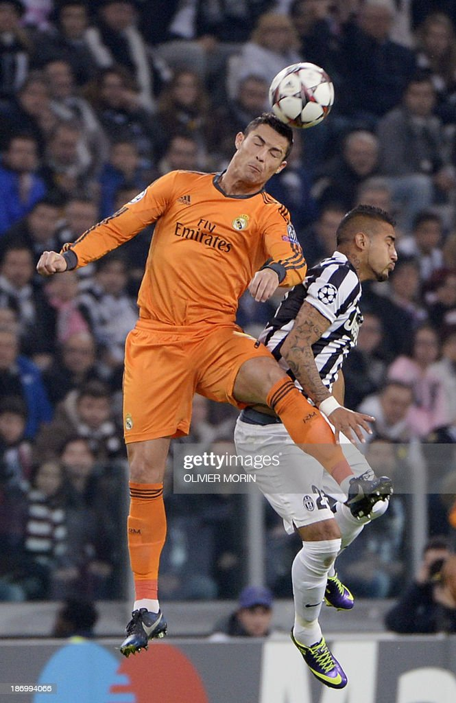 Real Madrid's Portuguese forward Cristiano Ronaldo jumps for the ball in front of Juventus' Chilean midfielder Arturo Vidal (R) on November 5, 2013 during a UEFA Champions League Group B football match at the Juventus stadium in Turin.