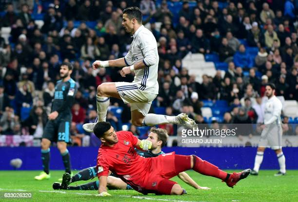 Real Madrid's Portuguese forward Cristiano Ronaldo jumps over Real Sociedad's Argentinian goalkeeper Geronimo Rulli during the Spanish league...