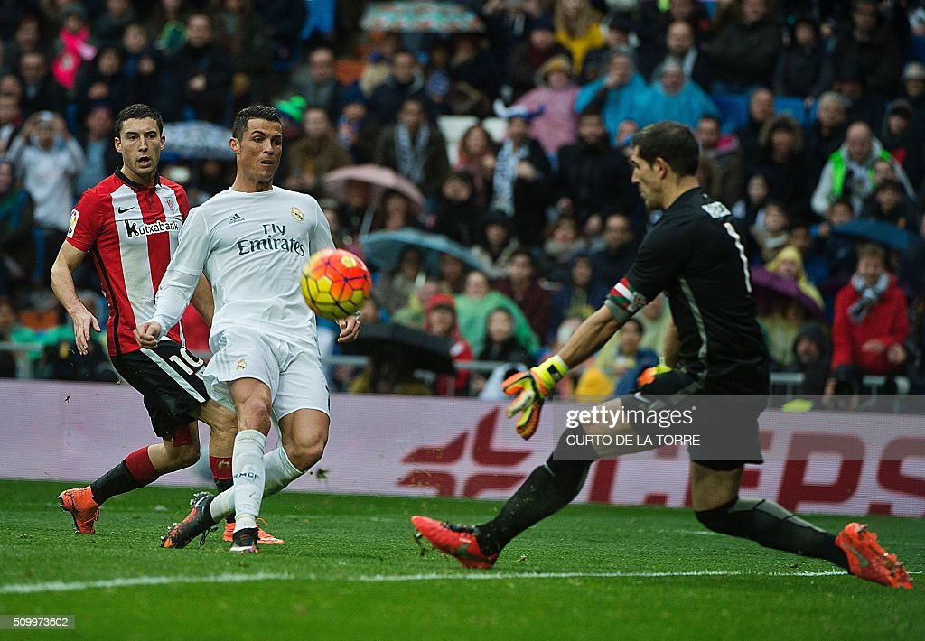Real Madrid's Portuguese forward Cristiano Ronaldo (C) kicks the ball past Athletic Bilbao's goalkeeper Gorka Iraizoz (R) during the Spanish league football match Real Madrid CF vs Athletic Club Bilbao at the Santiago Bernabeu stadium in Madrid on February 13, 2016. / AFP / CURTO DE LA TORRE