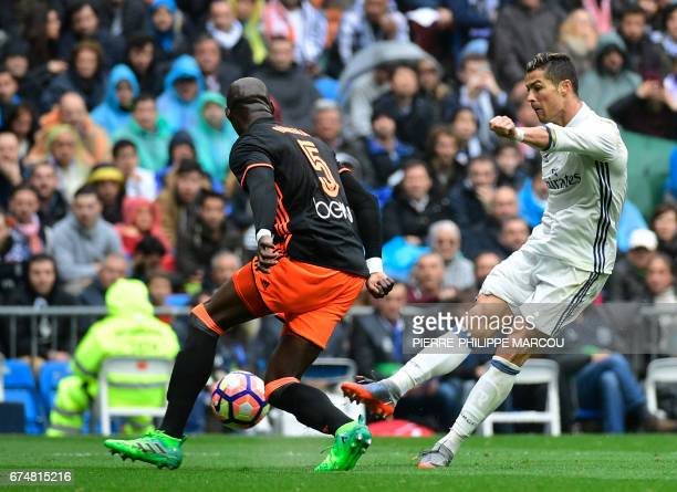 Real Madrid's Portuguese forward Cristiano Ronaldo kicks the ball beside Valencia's French defender Eliaquim Mangala during the Spanish league...