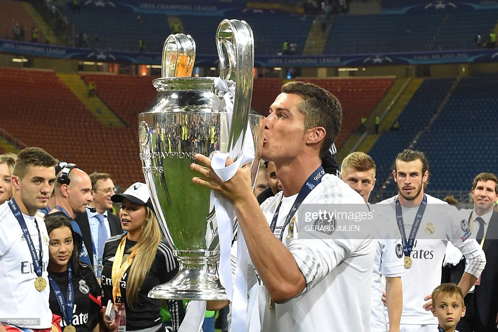 Real Madrid's Portuguese forward Cristiano Ronaldo kisses the trophy after Real Madrid won the UEFA Champions League final football match over Atletico Madrid at San Siro Stadium in Milan, on May 28, 2016. / AFP / GERARD