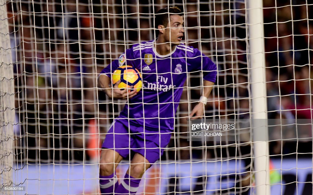 Real Madrid's Portuguese forward Cristiano Ronaldo olds the ball after scoring a goal during the Spanish league football match Valencia CF vs Real Madrid CF at the Mestalla stadium in Valencia on February 22, 2017. / AFP / JOSE