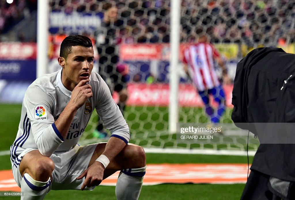 TOPSHOT - Real Madrid's Portuguese forward Cristiano Ronaldo poses in front of a TV camera as he celebrates after scoring during the Spanish league football match Club Atletico de Madrid vs Real Madrid CF at the Vicente Calderon stadium in Madrid, on November 19, 2016. Real Madrid won 3-0. / AFP / GERARD