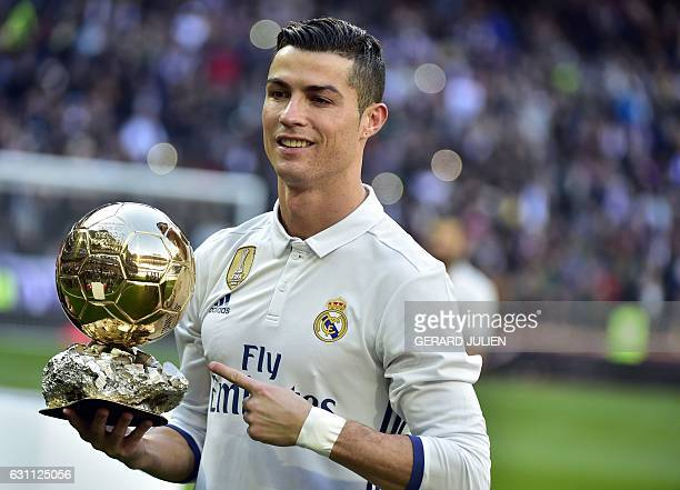 Real Madrid's Portuguese forward Cristiano Ronaldo poses with the Ballon d'Or France Football trophy before the Spanish league football match Real...