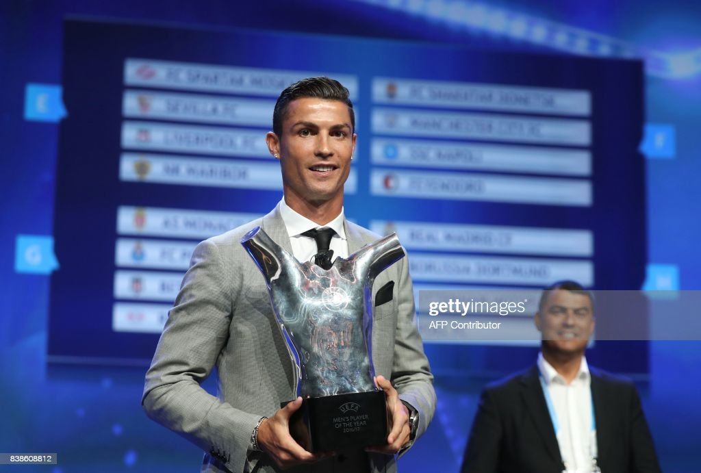 TOPSHOT - Real Madrid's Portuguese forward Cristiano Ronaldo poses with the trophy after he was awarded the title of 'Best Men's Player in Europe' at the conclusion of the UEFA Champions League group stage draw ceremony in Monaco on August 24, 2017. /