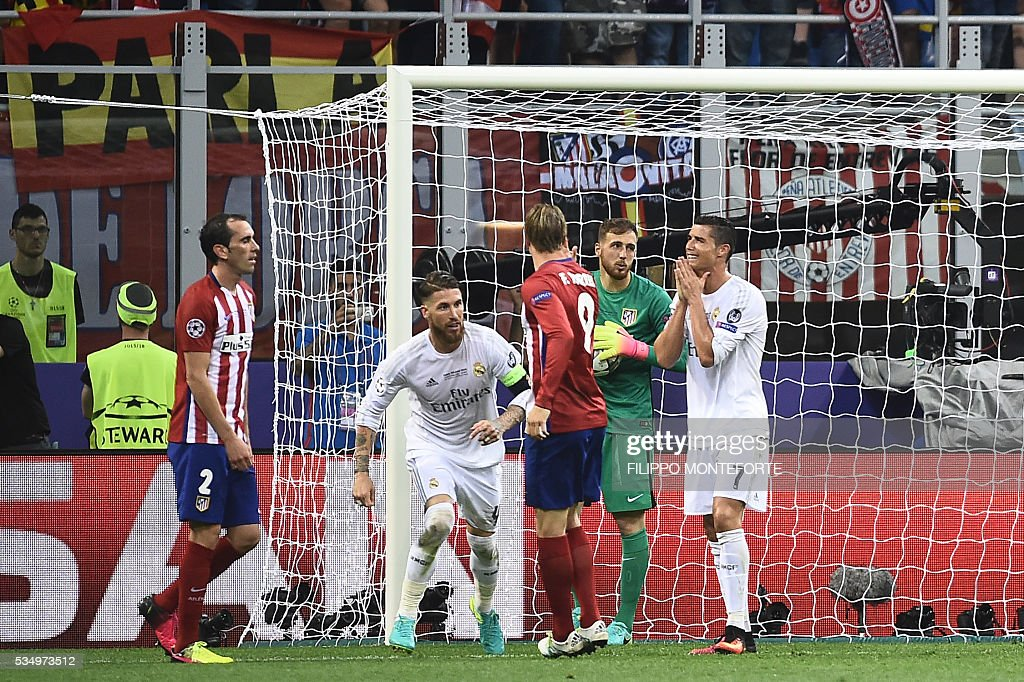Real Madrid's Portuguese forward Cristiano Ronaldo (R) reacts after missing a goal next to (R to L) Atletico Madrid's Slovenian goalkeeper Jan Oblak, Atletico Madrid's Spanish forward Fernando Torres, Real Madrid's Spanish defender Sergio Ramos and Atletico Madrid's Uruguayan defender Diego Godin during the UEFA Champions League final football match between Real Madrid and Atletico Madrid at San Siro Stadium in Milan, on May 28, 2016. / AFP / FILIPPO