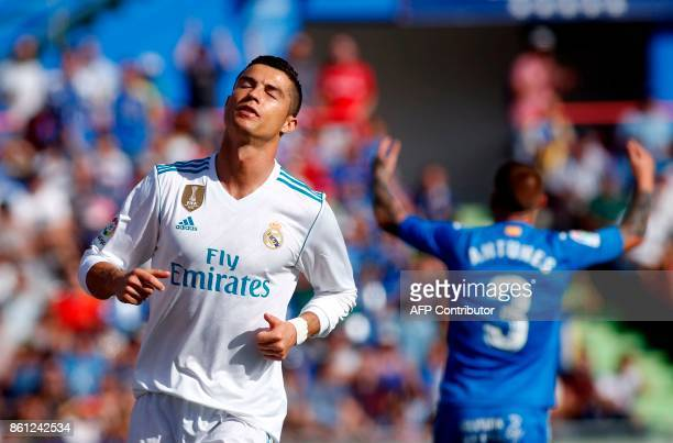 Real Madrid's Portuguese forward Cristiano Ronaldo reacts after missing a goal opportunity during the Spanish league football match Getafe CF vs Real...