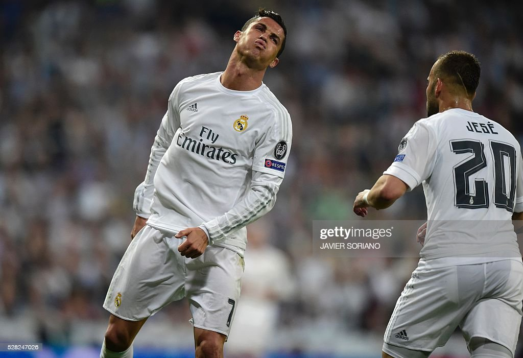 Real Madrid's Portuguese forward Cristiano Ronaldo (L) reacts past Real Madrid's forward Jese Rodriguez during the UEFA Champions League semi-final second leg football match Real Madrid CF vs Manchester City FC at the Santiago Bernabeu stadium in Madrid, on May 4, 2016. / AFP / JAVIER