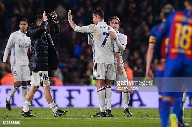 Real Madrid's Portuguese forward Cristiano Ronaldo Real Madrid's Croatian midfielder Luka Modric and teammates celebrate their 11 draw at the end of...