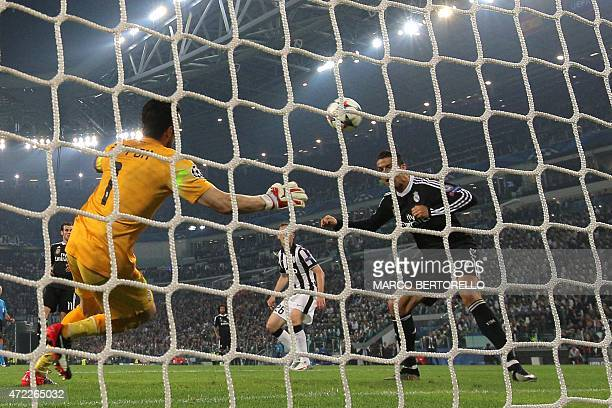 Real Madrid's Portuguese forward Cristiano Ronaldo scores against Juventus' goalkeeper and captain Gianluigi Buffon during the UEFA Champions League...
