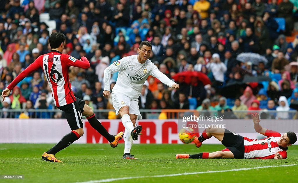 Real Madrid's Portuguese forward Cristiano Ronaldo (C) scores during the Spanish league football match Real Madrid CF vs Athletic Club Bilbao at the Santiago Bernabeu stadium in Madrid on February 13, 2016. / AFP / CURTO DE LA TORRE