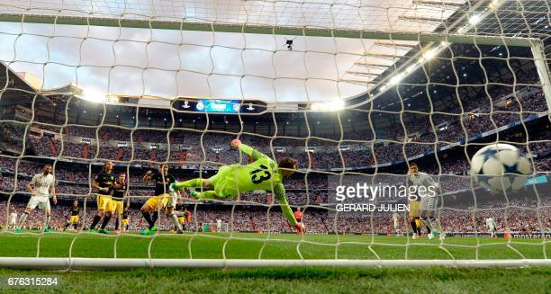 TOPSHOT Real Madrid's Portuguese forward Cristiano Ronaldo scores past Atletico Madrid's Slovenian goalkeeper Jan Oblak during the UEFA Champions...