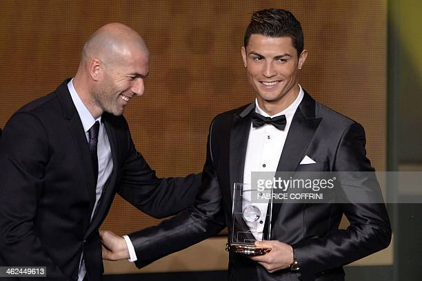 Real Madrid's Portuguese forward Cristiano Ronaldo shares a laugh with Real Madrid's assistant coach and former French midfielder Zinedine Zidane...