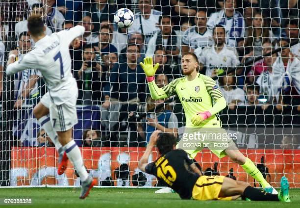 Real Madrid's Portuguese forward Cristiano Ronaldo shoots against Atletico Madrid's Slovenian goalkeeper Jan Oblak to score a goal during the UEFA...