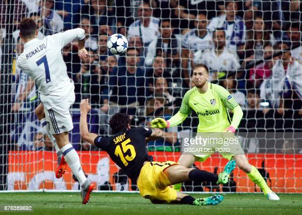 Real Madrid's Portuguese forward Cristiano Ronaldo shoots against Atletico Madrid's Slovenian goalkeeper Jan Oblak to score a goal during the UEFA...