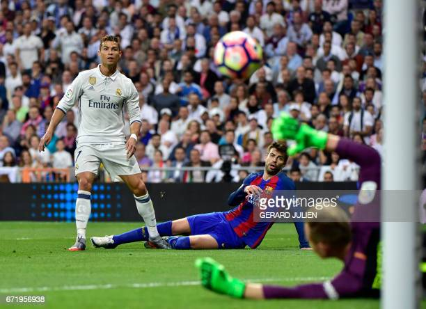 TOPSHOT Real Madrid's Portuguese forward Cristiano Ronaldo shoots beside Barcelona's defender Gerard Pique during the Spanish league football match...