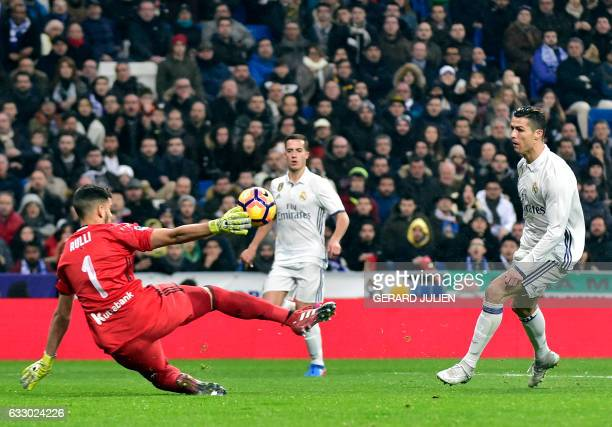 Real Madrid's Portuguese forward Cristiano Ronaldo shoots in front of Real Sociedad's Argentinian goalkeeper Geronimo Rulli to score a goal during...