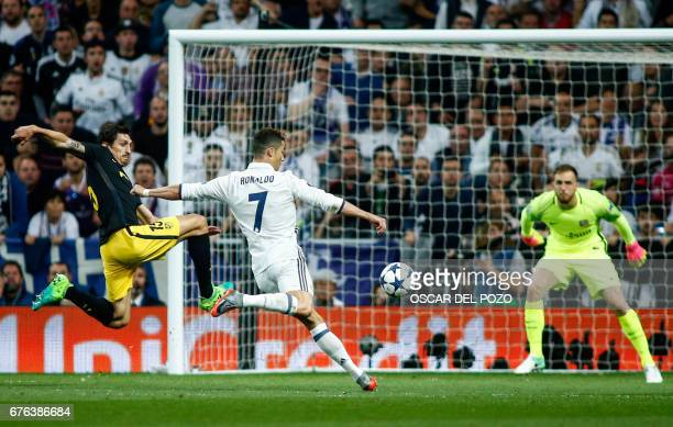 Real Madrid's Portuguese forward Cristiano Ronaldo shoots to score a goal beside Atletico Madrid's Montenegrin defender Stefan Savic during the UEFA...