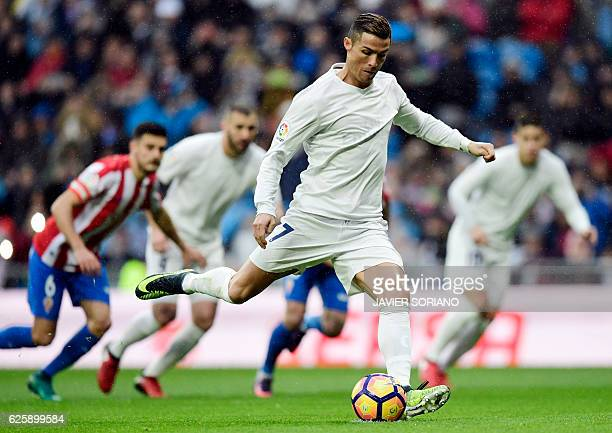 TOPSHOT Real Madrid's Portuguese forward Cristiano Ronaldo shoots to score the opening goal during the Spanish league football match Real Madrid CF...