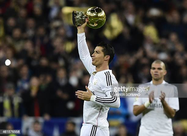 Real Madrid's Portuguese forward Cristiano Ronaldo shows the 2014 FIFA Ballon d'Or award for player of the year to his supporters prior to the...