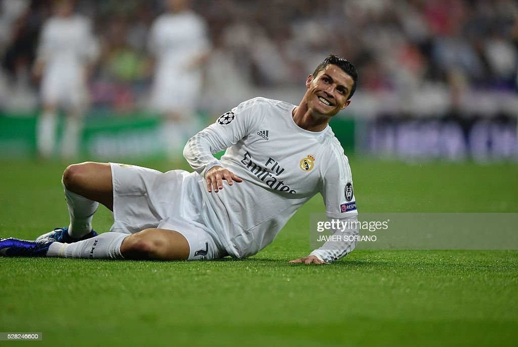 Real Madrid's Portuguese forward Cristiano Ronaldo smiles after falling on the pitch during the UEFA Champions League semi-final second leg football match Real Madrid CF vs Manchester City FC at the Santiago Bernabeu stadium in Madrid, on May 4, 2016. / AFP / JAVIER