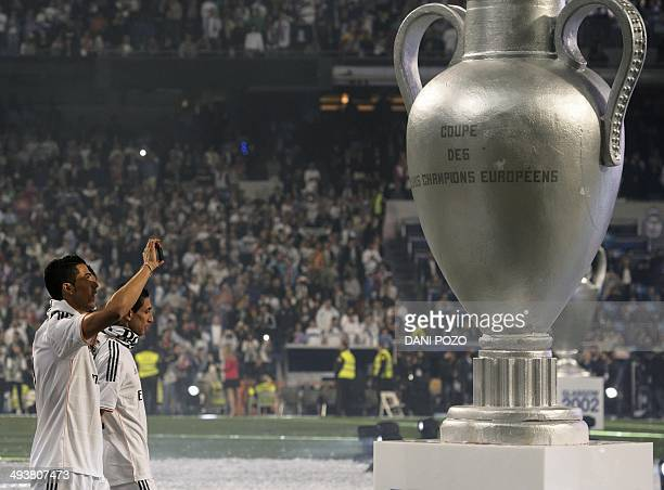 Real Madrid's Portuguese forward Cristiano Ronaldo takes pictures of a sculpture of the Champions League trophy as Real Madrid's players celebrate...