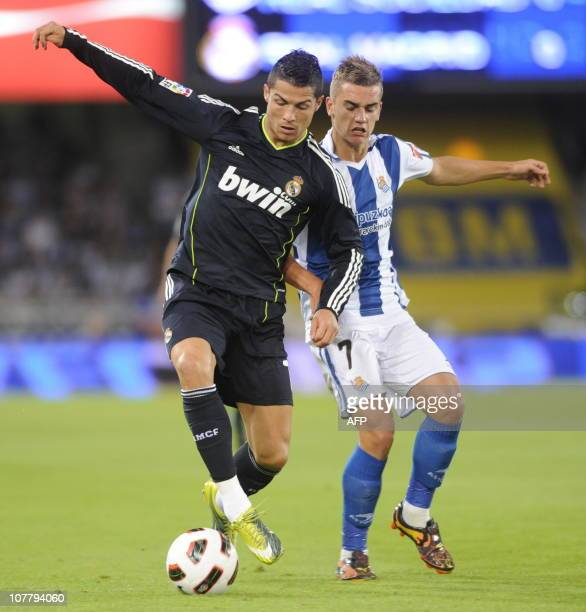 Real Madrid's Portuguese forward Cristiano Ronaldo vies for the ball with Real Sociedad's French forward Antoine Griezmann during a Spanish league...