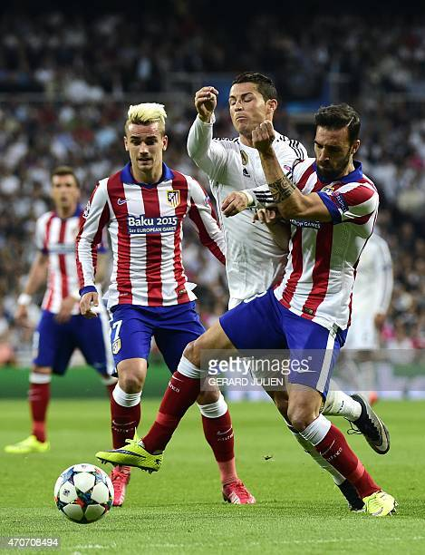 Real Madrid's Portuguese forward Cristiano Ronaldo vies with Atletico Madrid's defender Jesus Gamez and Atletico Madrid's French forward Antoine...