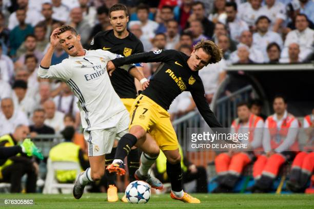 Real Madrid's Portuguese forward Cristiano Ronaldo vies with Atletico Madrid's French forward Antoine Griezmann during the UEFA Champions League...
