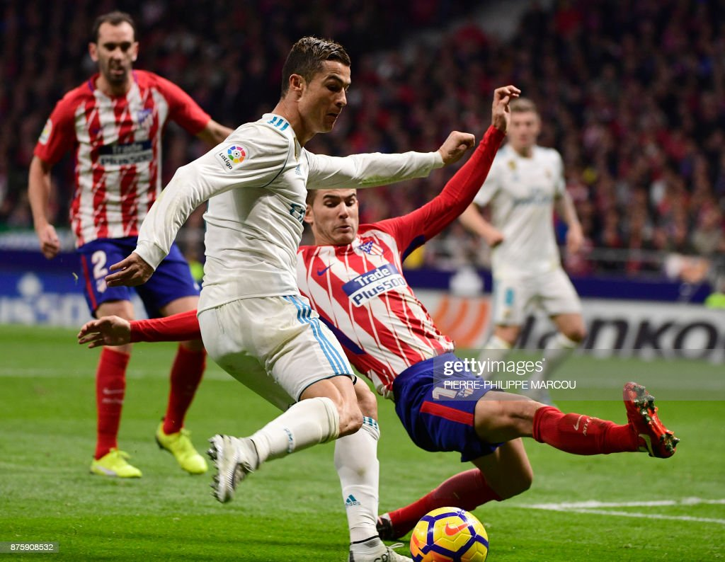 Real Madrid's Portuguese forward Cristiano Ronaldo (L) vies with Atletico Madrid's French defender Lucas Hernandez during the Spanish league football match Atletico Madrid vs Real Madrid at the Wanda Metropolitan stadium in Madrid on November 18, 2017. /