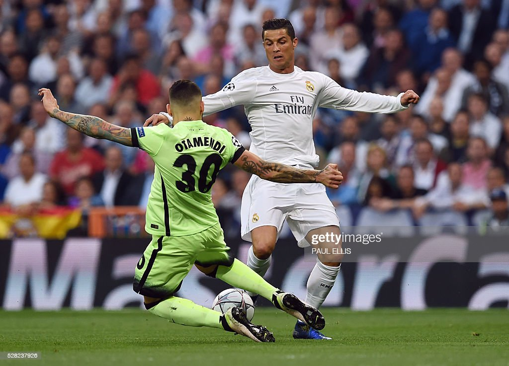 Real Madrid's Portuguese forward Cristiano Ronaldo (R) vies with Manchester City's Argentinian defender Nicolas Otamendi during the UEFA Champions League semi-final second leg football match Real Madrid CF vs Manchester City FC at the Santiago Bernabeu stadium in Madrid, on May 4, 2016. / AFP / PAUL