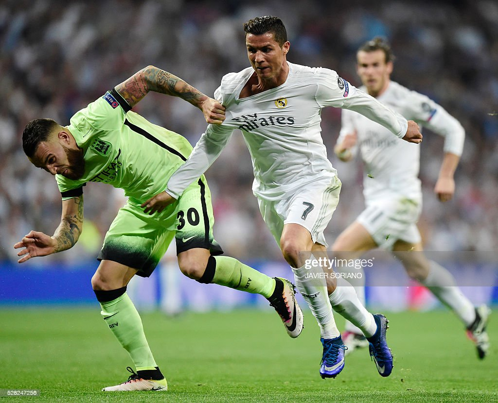 Real Madrid's Portuguese forward Cristiano Ronaldo (C) vies with Manchester City's Argentinian defender Nicolas Otamendi (L) during the UEFA Champions League semi-final second leg football match Real Madrid CF vs Manchester City FC at the Santiago Bernabeu stadium in Madrid, on May 4, 2016. / AFP / JAVIER