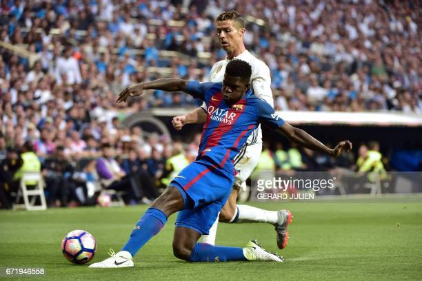 Real Madrid's Portuguese forward Cristiano Ronaldo vies with Barcelona's French defender Samuel Umtiti during the Spanish league football match Real...