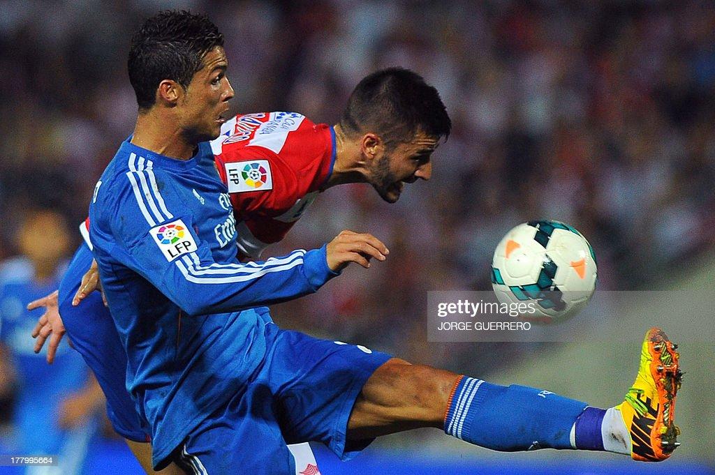 Real Madrid's Portuguese forward Cristiano Ronaldo vies with Granada's midfielder Fran Rico during the Spanish league football match Granada FC vs...